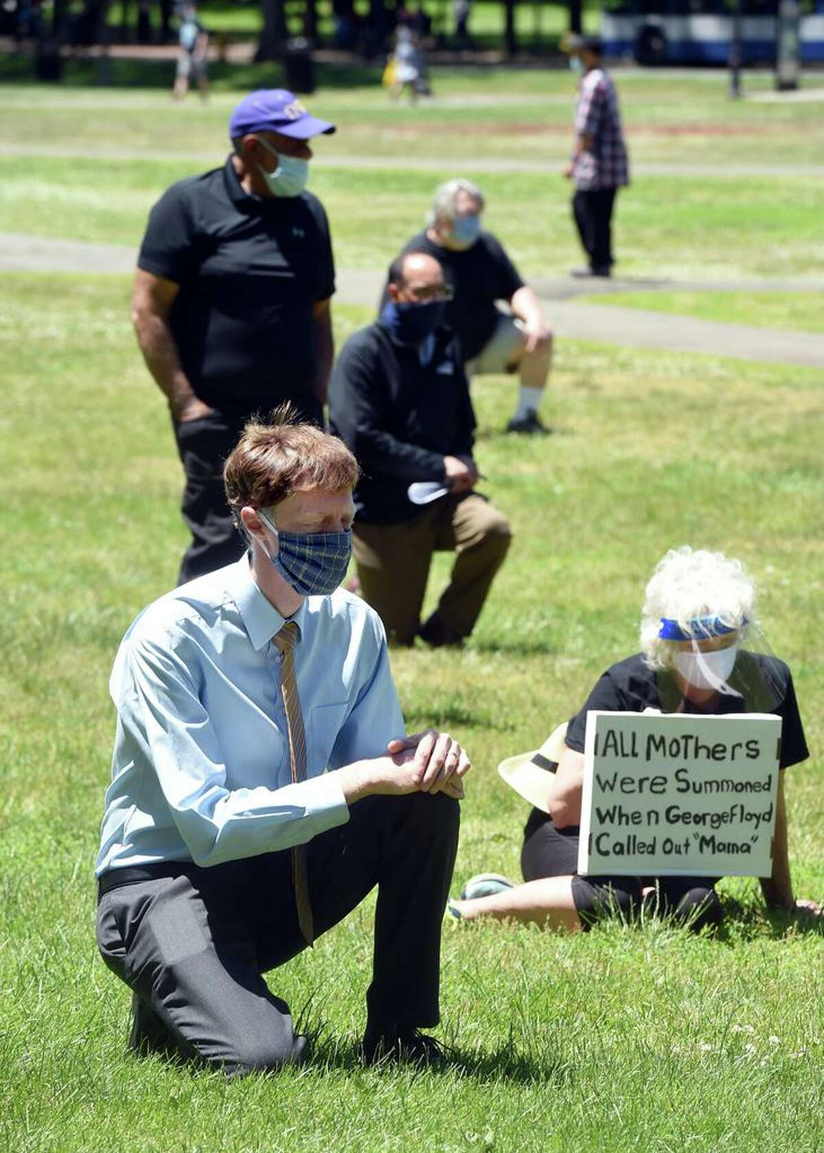 New Haven Mayor Justin Elicker (foreground) takes a knee in silence, the time George Floyd was pinned to the ground before his death at the hands of Minneapolis police, with others during an elder protest to support black lives, oppose police brutality and support institutional change on the New Haven Green on Monday .
