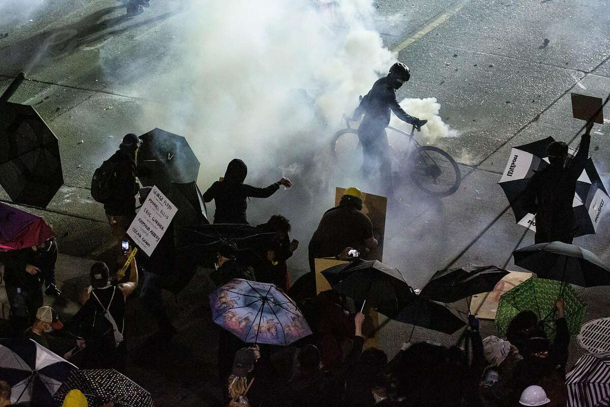 SEATTLE, WA - JUNE 08: Demonstrators clash with law enforcement near the Seattle Police Departments East Precinct shortly after midnight on June 8, 2020 in Seattle, Washington. Earlier in the evening, a suspect drove into the crowd of protesters and shot one person, which happened after a day of peaceful protests across the city. Later, police and protestors clashed violently during ongoing Black Lives Matter demonstrations following the death of George Floyd. (Photo by David Ryder/Getty Images)