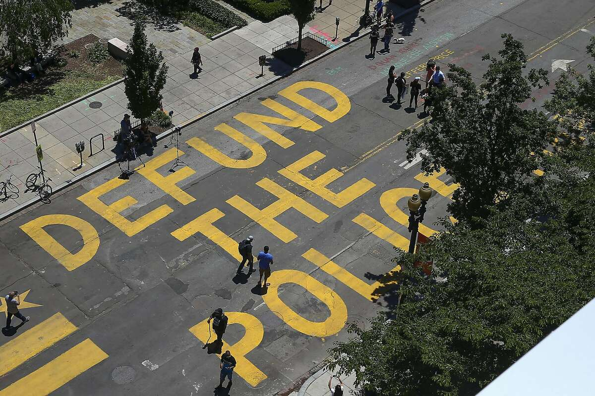 WASHINGTON, DC - JUNE 08: People walk down 16th street after Defund The Police was painted on the street near the White House on June 08, 2020 in Washington, DC. After days of protests in DC over the death of George Floyd, DC Mayor Muriel Bowser has renamed that section of 16th street