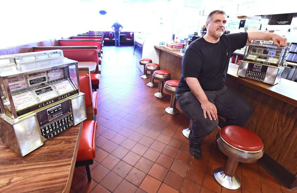 Lou Mihalakos, co-owner of Clark's Pizza and Restaurant in New Haven, sits with jukeboxes that used to be installed at the eatery. The eatery has permanently closed its doors.