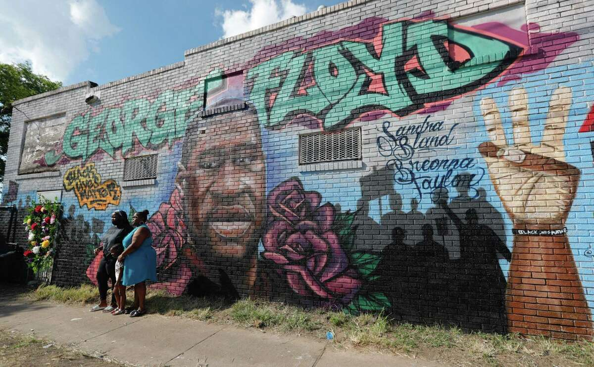 A family takes a photo in front of a mural in honor of George Floyd near the intersection of Elgin Street and Ennis Street, Monday, June 8, 2020, in Houston.