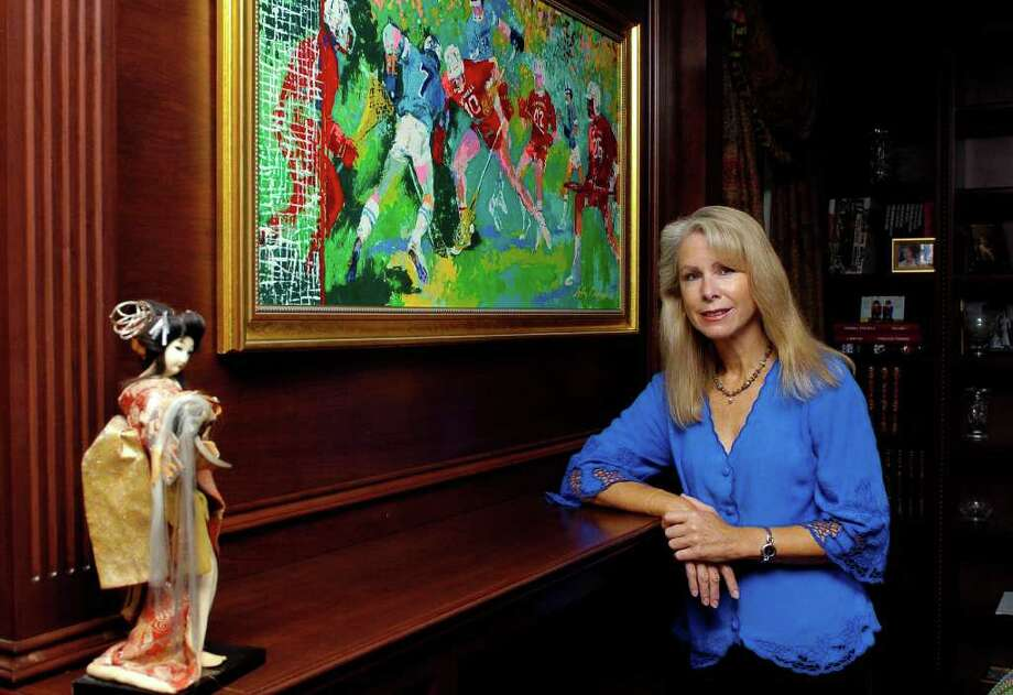 Bonnie McEneaney stands by a painting by LeRoy Neiman of her husband playing lacrosse in the den of her home in New Canaan, Conn. on Monday August 23, 2010.  McEneaney has written a book, titled Messages, about premonitions or signs that she says 9/11 victims have sent their still-living family from beyond, her husband, Eamon, was killed in the WTC. Photo: Dru Nadler / Stamford Advocate Freelance