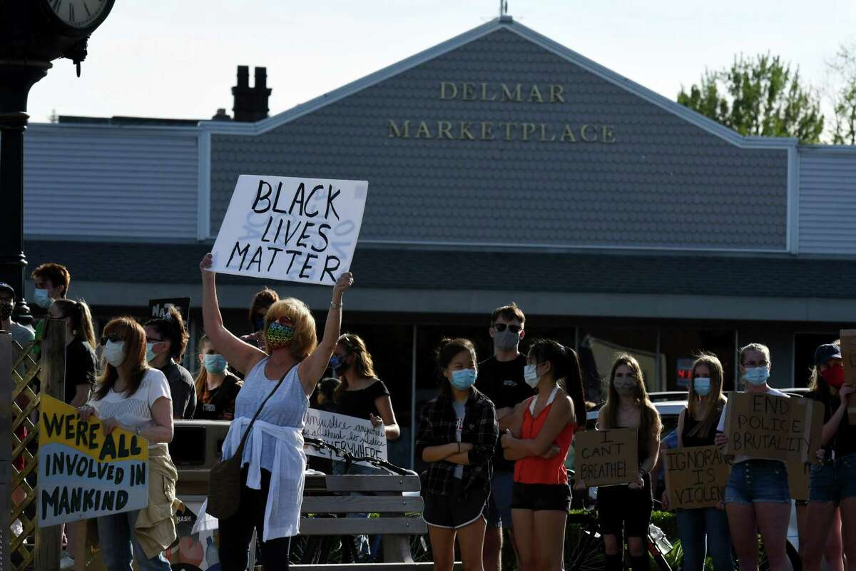 People gather in solidarity at the Four Corners during a vigil to protest against police brutality and inequality in the wake of the death of George Floyd on Monday, June 8, 2020, in Delmar, N.Y. (Will Waldron/Times Union)