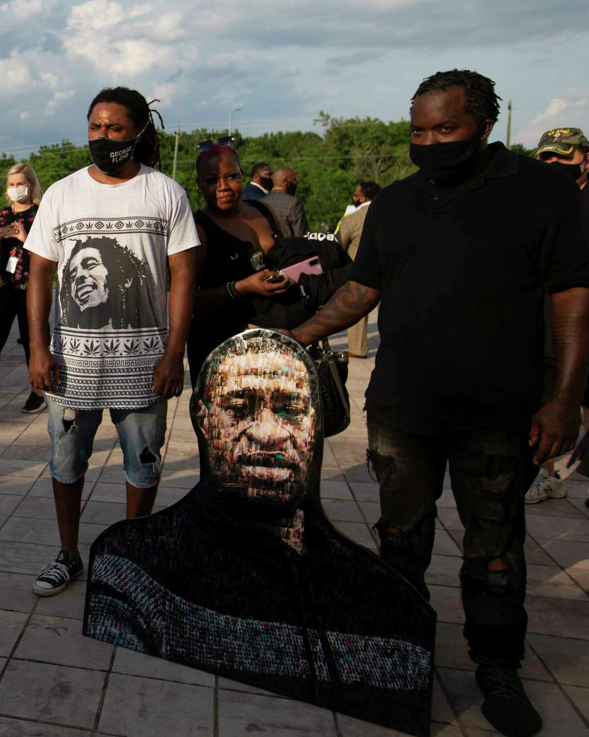 People bring a photo mosaic of George Floyd to the public mamorial for him Monday, June 8, 2020, at The Fountain of Praise Church in Houston.