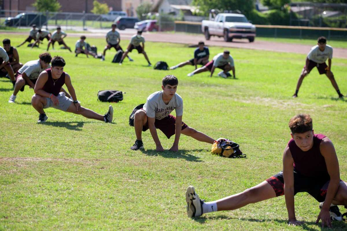 Players stretch with at least six feet between each other during the first day of strength and conditioning camp at San Antonio's Harlandale High School on Monday.