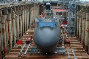 Defense contractors such as Electric Boat will buffer Connecticut in the recession and recovery, but the state's weaknesses remain as the nation recovers from 40 million job losses in the Coronavirus shutdown. In this Thursday, July 30, 2015 photo, shipyard workers at General Dynamics Electric Boat prepare the submarine Illinois for float-off in Groton, Conn.