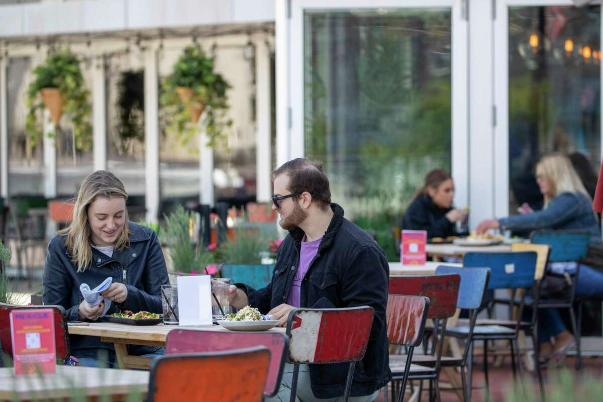Emily Black, left, and Adam Weinstein have lunch on the outdoor patio of Mexicue restaurant, Wednesday, May 20, 2020, in Stamford, Conn. Restaurants offered outdoor service starting May 20 as part of the first phase of Connecticut's statewide reopening, including in hard-hit Fairfield County on the New York state line. (AP Photo/Mary Altaffer)
