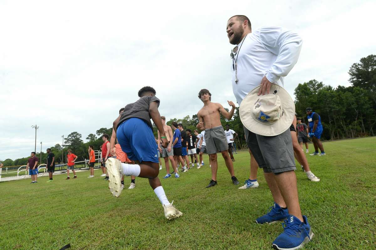 Coach Jason Smith watches as Kelly High School's football team gets in its first practice of the 2020 season Monday morning. It was the first day that team practices were allowed in the state under guidelines issued to schools by TAPPS and UIL. Photo taken Monday, June 8, 2020 Kim Brent/The Enterprise