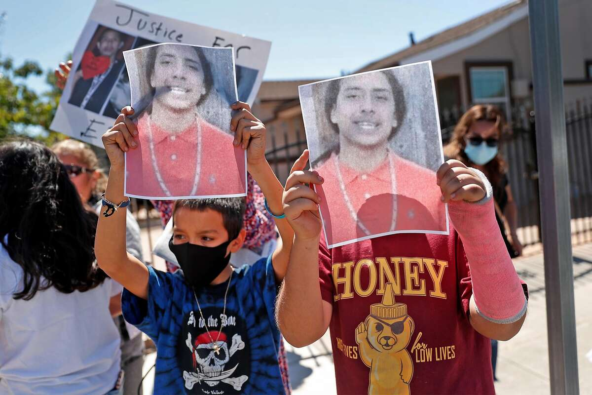 Erik Salgado's cousins Angel Guzman, 11, (left) and Eric Beltran, 11, hold up photos of Salgado as people gather at Elmhurst Middle School to protest the death of and memorialize the life of Salgado, who was killed in a CHP officer-involved shooting Saturday night. Photographed in Oakland, Calif., on Monday, June 8, 2020.