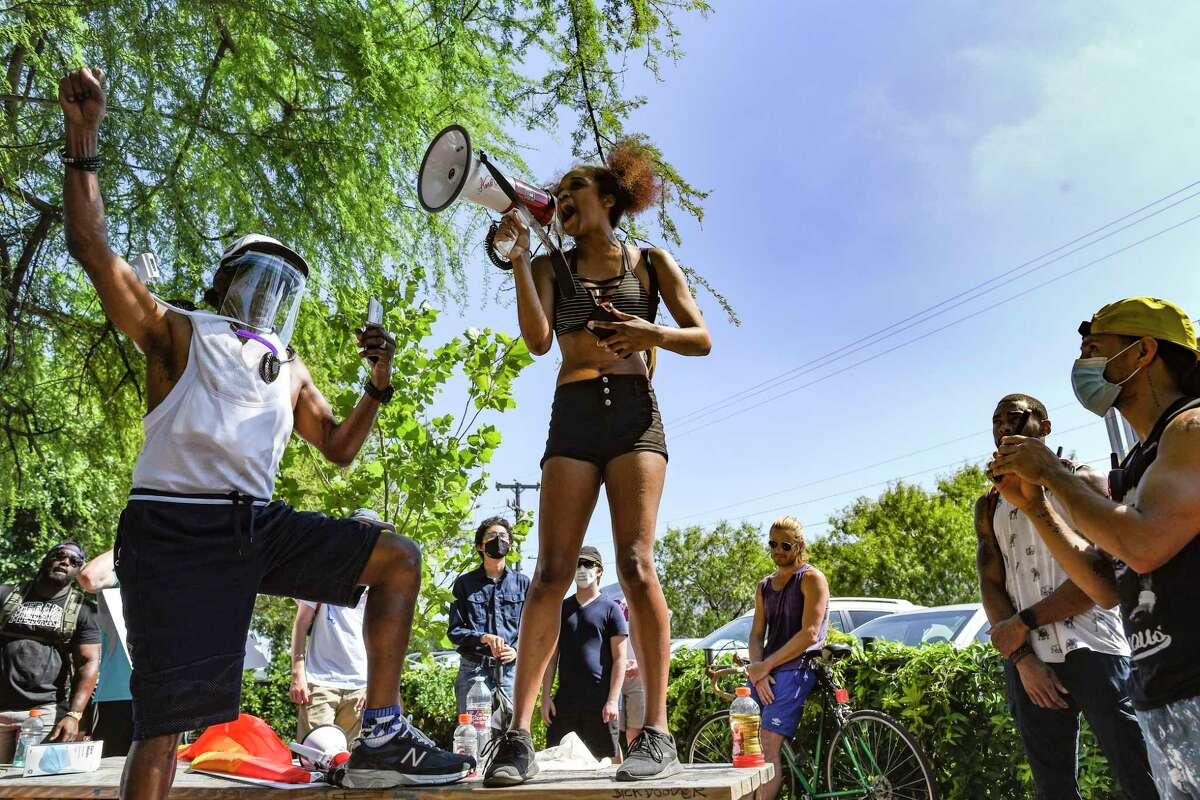 """Lexi Qaiyyim recites """"Still I Rise,"""" a poem by Maya Angelou, during a protest at the Blue Star Arts Complex on Monday, June 8, 2020. People attending the event called for changes in policing and honored George Floyd, an African-American man who died at the hands of police in Minneapolis."""
