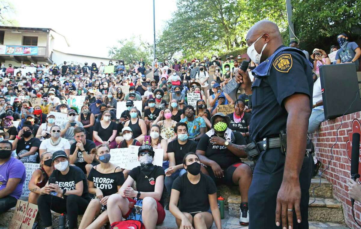 Officer Douglas Greene of the San Antonio Police Department makes a conciliatory speech to the crowd during a recent protest. The task ahead is to channel this energy into policy.
