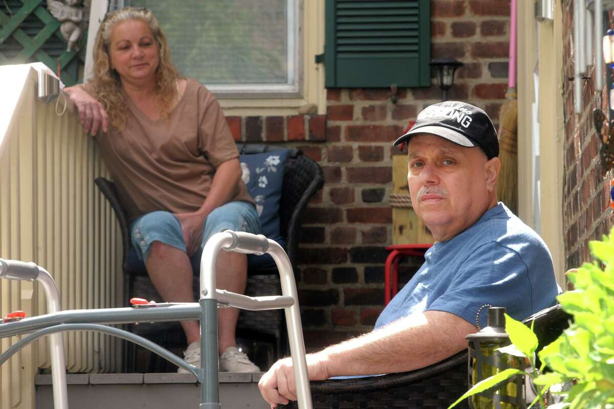 Raymond Piccinino poses in front of his home in Bridgeport, Conn. June 1, 2020. Piccinino, is an employee at St. Vincent's Medical Center, where he was also treated for coronavirus. He is seen here with his wife, Elaine.