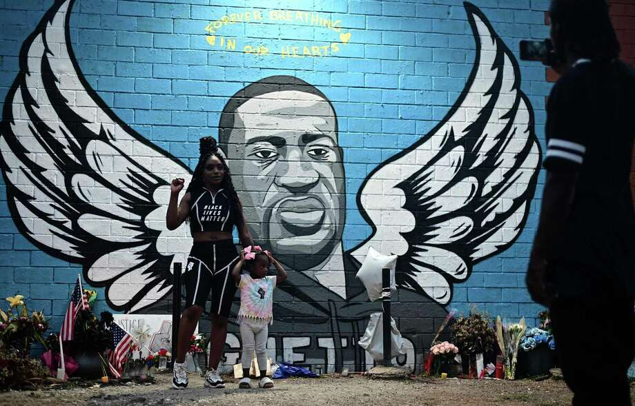 TOPSHOT - People stand in front of a mural of George Floyd in Houston, Texas on June 8, 2020. - George Floyd, the 46-year-old African American whose killing by a white police officer transformed him into a global icon of the struggle against racism and police brutality, will be laid to rest on June 9 in Houston, the city where he grew up. (Photo by Johannes EISELE / AFP) (Photo by JOHANNES EISELE/AFP via Getty Images) Photo: JOHANNES EISELE / AFP Via Getty Images / AFP or licensors