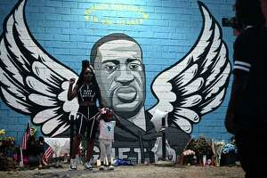 TOPSHOT - People stand in front of a mural of George Floyd in Houston, Texas on June 8, 2020. - George Floyd, the 46-year-old African American whose killing by a white police officer transformed him into a global icon of the struggle against racism and police brutality, will be laid to rest on June 9 in Houston, the city where he grew up. (Photo by Johannes EISELE / AFP) (Photo by JOHANNES EISELE/AFP via Getty Images)