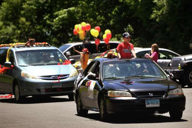 Sunnyside School teachers greet an automobile parade of students and their parents to mark the end of the school year on Monday.