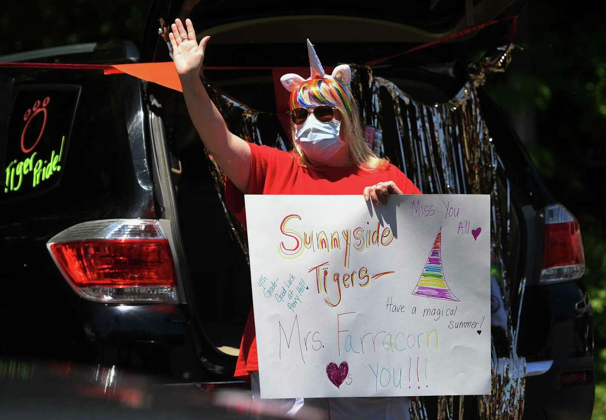 Sunnyside School special education tutor Gina Farra greets an automobile parade of students and their parents to mark the end of the school year on Monday. Cars were decorated for the occasion and many students held signs thanking their teachers.