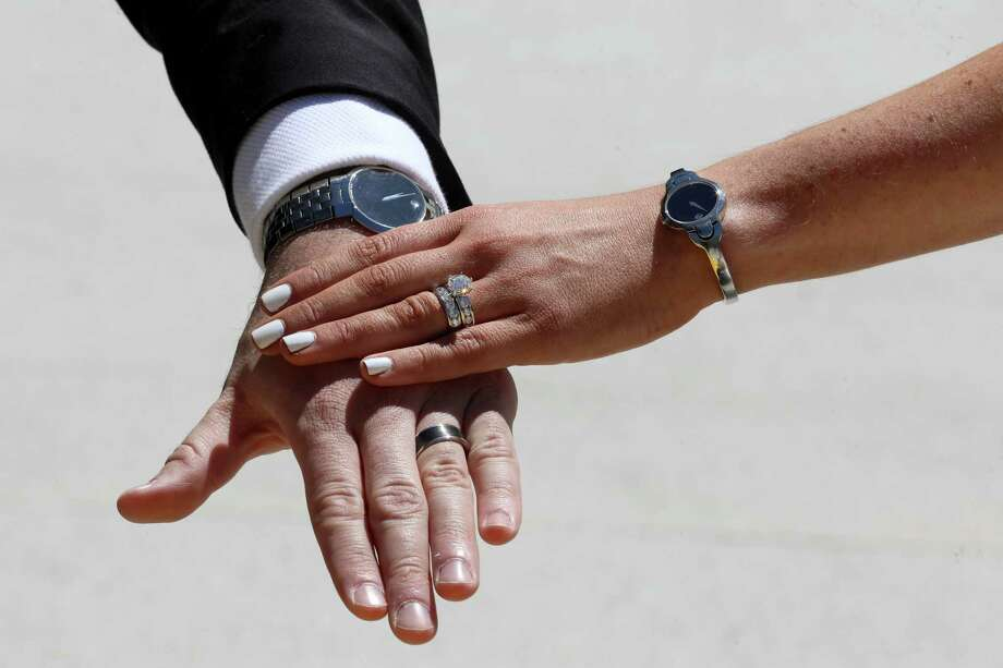 Lindsay and Dustin Schneider show off their wedding rings following their marriage ceremony at the Chase Center, with Golden State Warriors rookie Jordan Poole as their witness in San Francisco on May 23. The couple had been scheduled to get married on May 23 in Orlando (big Disney fans). Due to coronavirus those plans were scrapped, so they approached the Warriors about getting married outside Chase. The Warriors said yes. Photo: Yalonda M. James / The Chronicle / ONLINE_YES