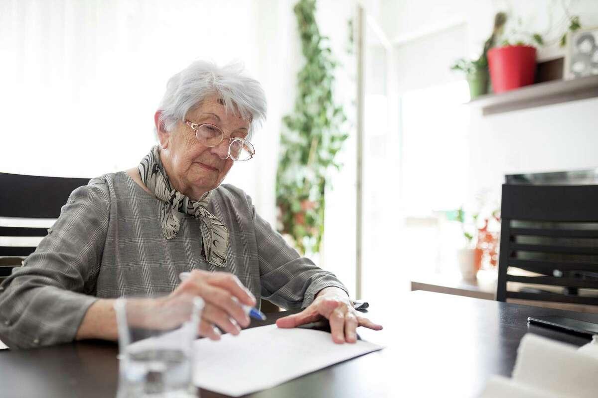 Senior woman doing Alzheimer's disease or dementia clock drawing self assessment test.