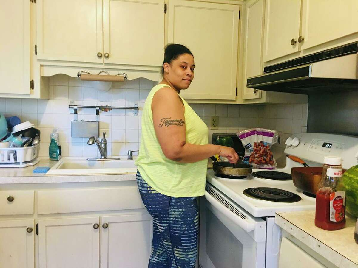 Tameeka Coleman of Bridgeport prepares a meal for her six younger children while taking a break from caring for her newborn.