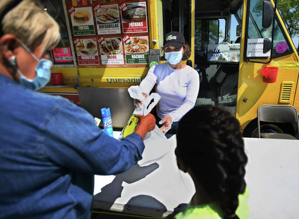 Andrea Figueroa of West Haven waits on customers at a food truck at Long Wharf in New Haven May 26, 2020. The trucks were forced to close when the coronavirus pandemic hit to address health department concerns including the use of masks and social distancing.