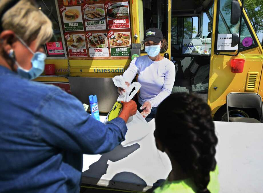Andrea Figueroa of West Haven waits on customers at a food truck at Long Wharf in New Haven May 26, 2020. The trucks were forced to close when the coronavirus pandemic hit to address health department concerns including the use of masks and social distancing. Photo: Brian A. Pounds / Hearst Connecticut Media File / Connecticut Post