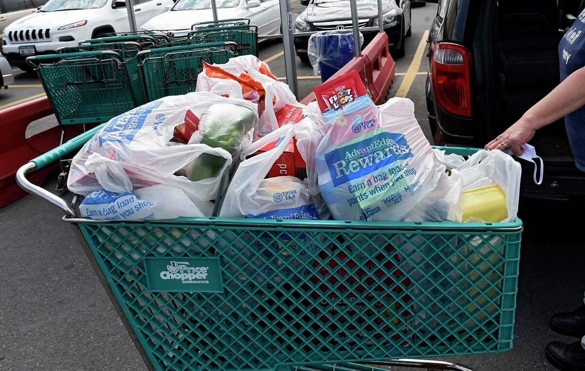 A shopper gets ready to unload her groceries from her cart to her car in the Price Chopper parking lot on Central Ave. Tuesday, June 9, 2020 in Albany, N.Y. Environmentalists are pushing the state to implement the plastic bag ban put off when the coronavirus hit. (Lori Van Buren/Times Union)