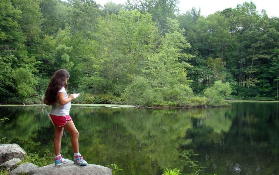 A young visitor enjoys solitude at Weir Pond at Weir Farm, a national historic site located in Wilton and Ridgefield. Photo: National Park Service Photo