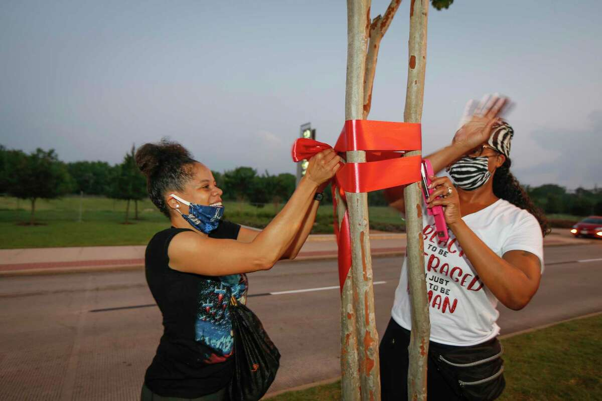 Jennifer Plummer and Natile Farris tie ribbons to honor George Floyd. Moms of Pearland coordinated with the city and Pearland Police to tie ribbons around along the funeral procession route for Floyd on Tuesday, June 9, 2020, in Pearland.