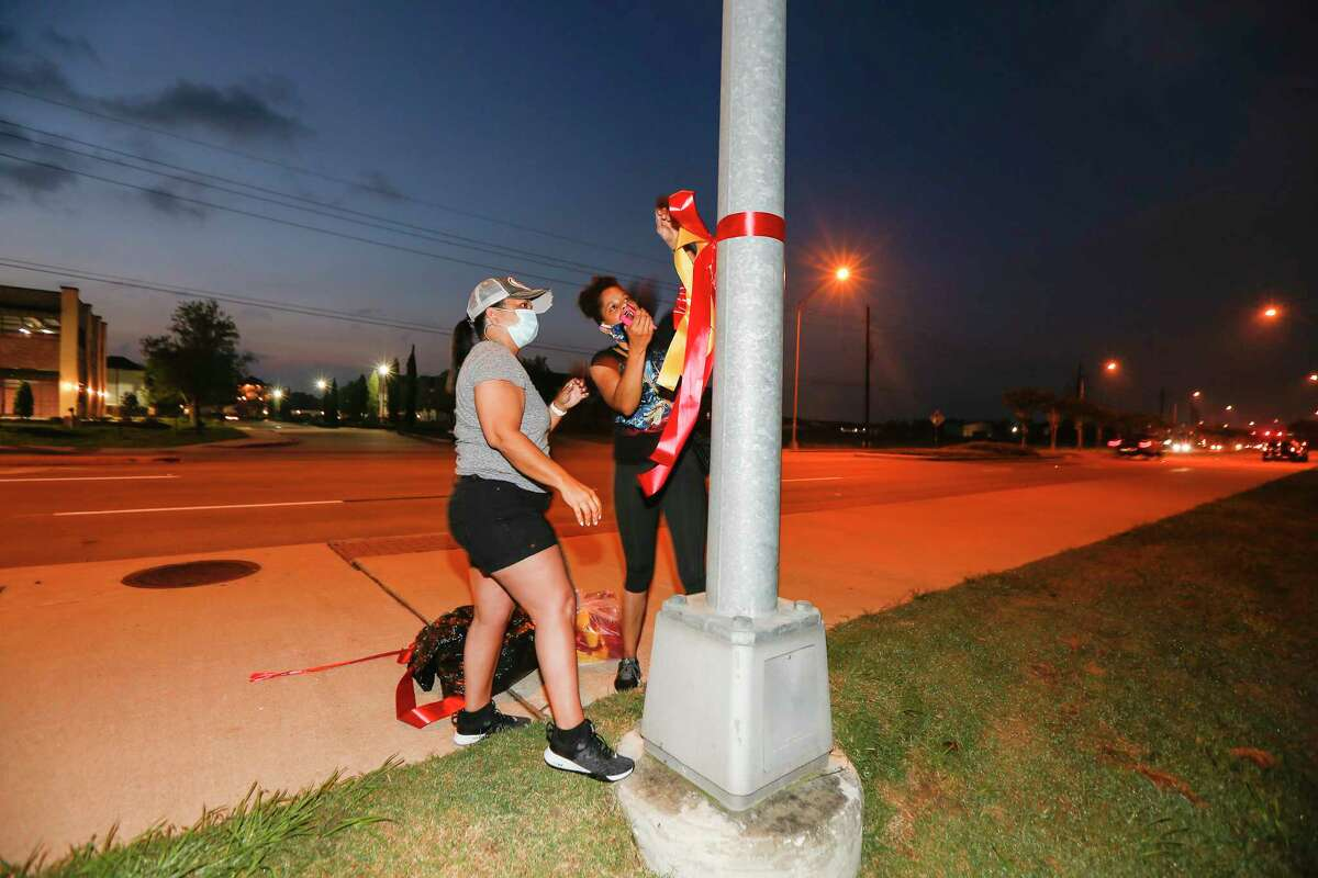 Emily Doucet and Jennifer Plummer tie ribbons to honor George Floyd. Moms of Pearland coordinated with the city and Pearland Police to tie ribbons around along the funeral procession route for Floyd on Tuesday, June 9, 2020, in Pearland.