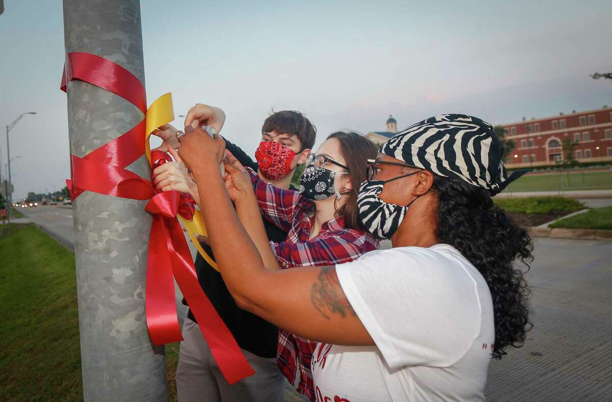 J.C. Yordy (l-r), his sister Kate Yordy and Natile Farris tie ribbons to honor George Floyd. They decorated the funeral route for Floyd in Pearland on Tuesday, June 9, 2020.
