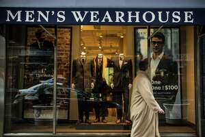 A man walks past a Men's Warehouse store in New York City.