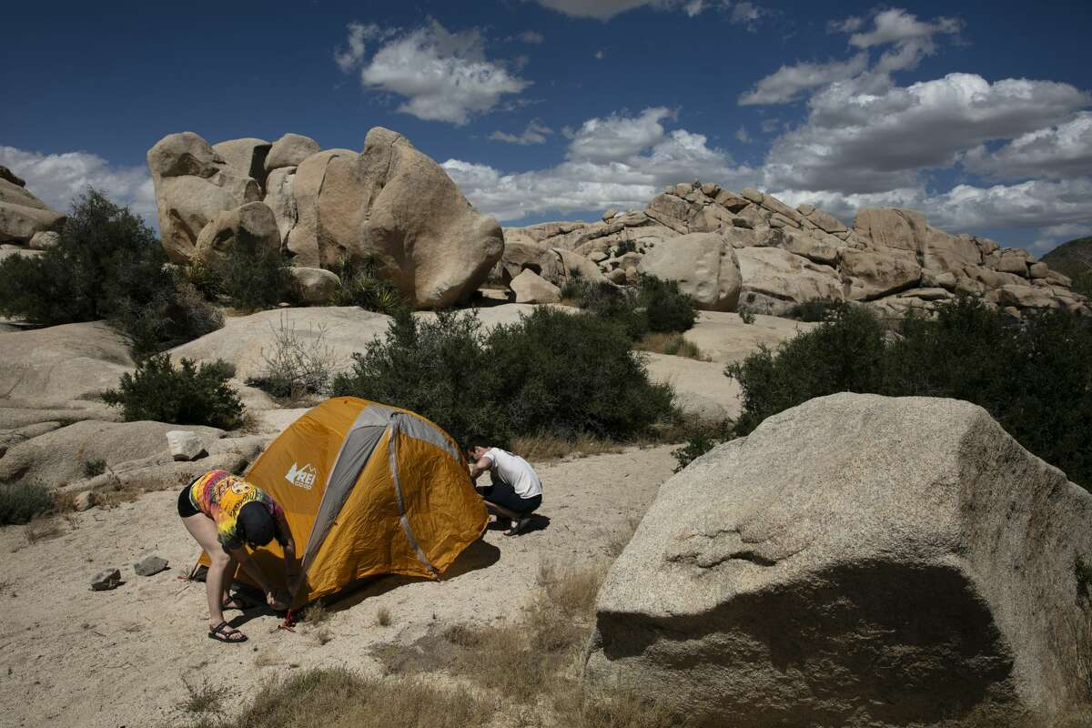 In this May 19, 2020, file photo, Marta Jerebets, left, and Arthur Pettit pitch their tent on a campground at Joshua Tree National Park in California. California will allow schools, day camps, bars, gyms, campgrounds and professional sports to begin reopening with modifications starting Friday, June 12, 2020.