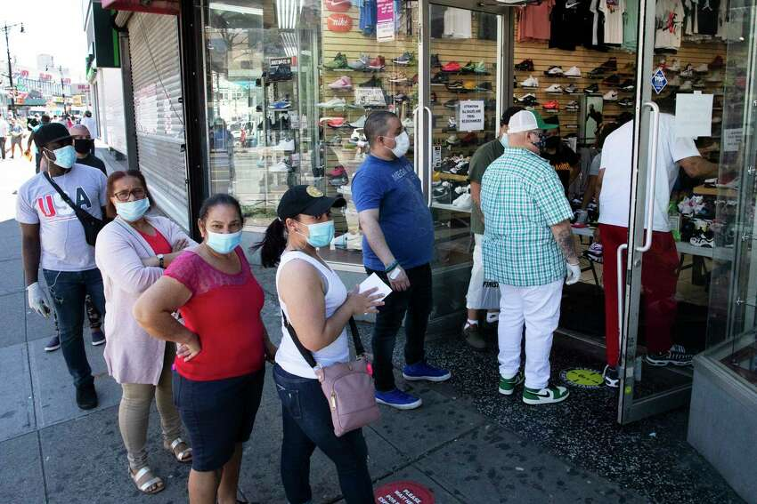 People with their face masks stand in line to enter a Sneaker Box after it reopens, Monday, June 8, 2020, in the Bronx borough of New York. After three bleak months, New York City will try to turn a page when it begins reopening Monday after getting hit first by the coronavirus, then an outpouring of rage over racism and police brutality.