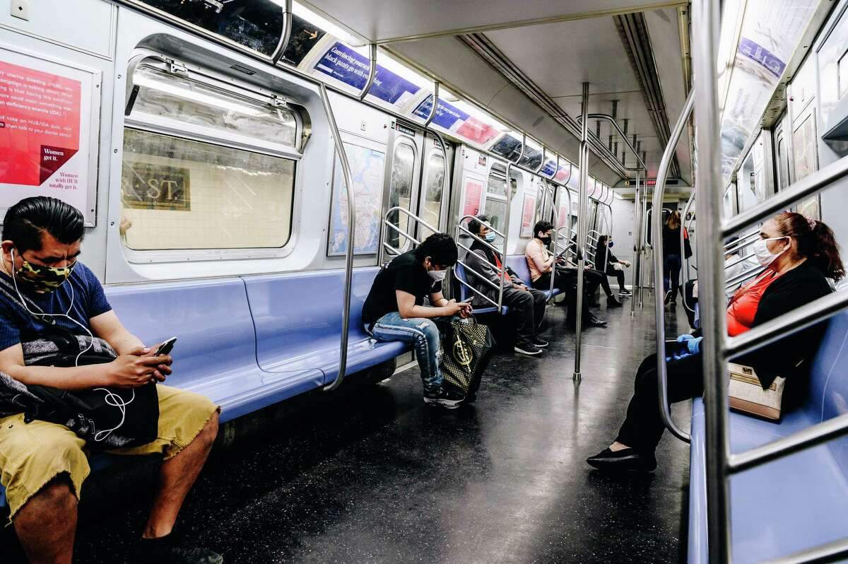 """Commuters wearing protective masks ride the L subway line during rush hour in the Williamsburg neighborhood in the Brooklyn borough of New York, U.S., on Monday, June 8, 2020. Only 1.2% of New Yorkers tested Sunday were infected with the new coronavirus, the lowest rate since the pandemic began. """"Why are wereopening? Because these numbers say we can,"""" GovernorAndrew Cuomosaid said at a news conference in Manhattan. Photographer: Nina Westervelt/Bloomberg"""