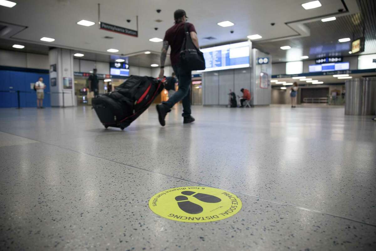 A traveler walks past a social distancing marker at Pennsylvania Station in New York, U.S., on Monday, June 8, 2020. Only 1.2% of New Yorkers tested Sunday were infected with the new coronavirus, the lowest rate since the pandemic began.