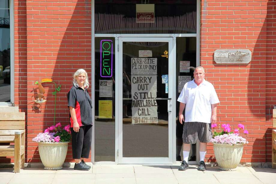 Helen and Kevin Wiley outside of their restaurant, the Pasta House in Kinde. They are holding off on opening back up for sit-down service for a few weeks. (Robert Creenan/Huron Daily Tribune)