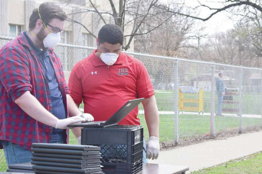Logan Tannahill (left) and Javonn Gardner of Jacksonville School District 117's technology department prepare laptops for student pickup to assist with distance learning during the COVID-19 pandemic. The state has started the process of returning some students to in-person lessons this summer. Photo: Samantha McDaniel-Ogletree | Journal-Courier