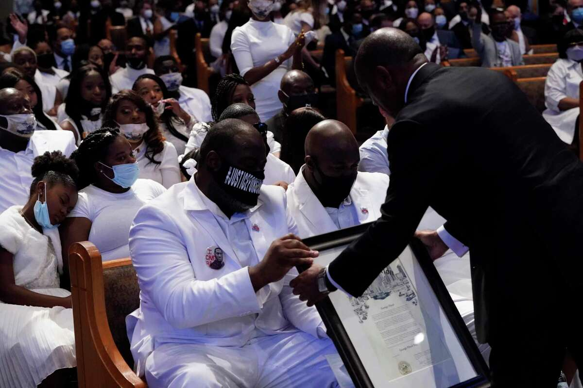 Houston Mayor Sylvester Turner hands the family a proclomation family and guests attend the funeral service for George Floyd at The Fountain of Praise church Tuesday, June 9, 2020, in Houston.