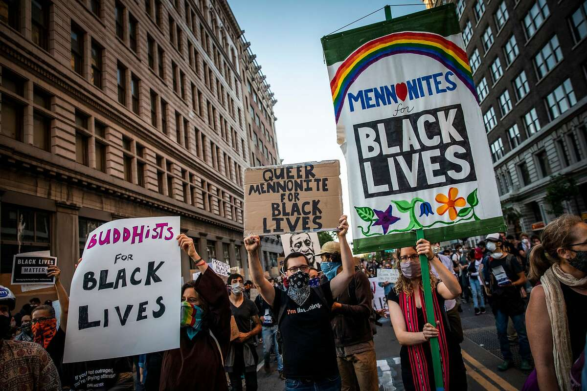 """Demonstrators from various faith groups arrive to attend a """"Sit Out the Curfew"""" protest against the death of George Floyd who died on May 25 in Minneapolis whilst in police custody, along a street in Oakland, California on June 3, 2020."""