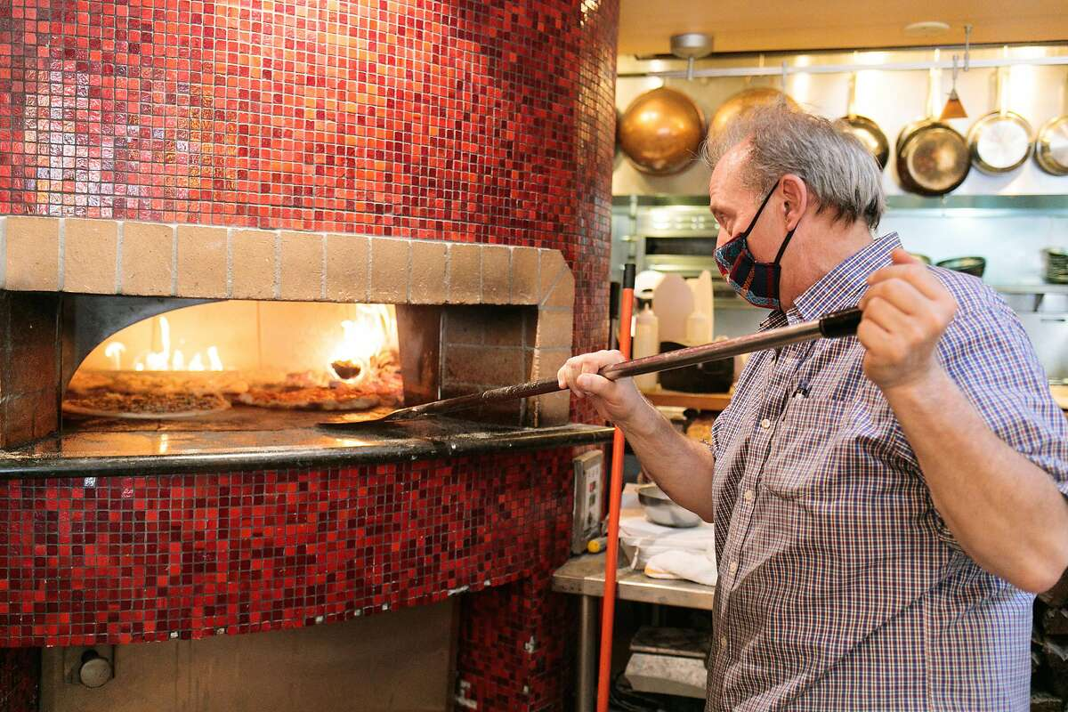 Andy Gambardella moves pizzas around in the pizza oven at Pazzo in San Carlos.