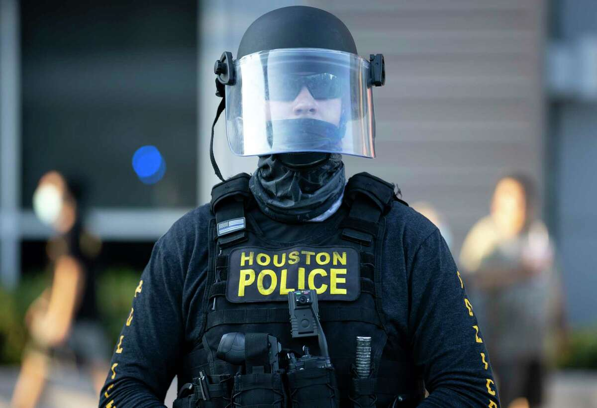 A Houston Police Department officer wears a face mask and shield during a protest held in downtown Houston, Tuesday, June 3, 2020. An estimated 60,000 people attended the rally in support of George Floyd and police reform.