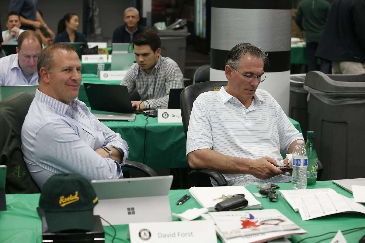 OAKLAND, CA - JUNE 3: General Manager David Forst and Executive Vice President of Baseball Operations Billy Beane of the Oakland Athletics sit in the Athletics draft room, during the opening day of the 2019 MLB draft, at the Oakland-Alameda County Coliseu