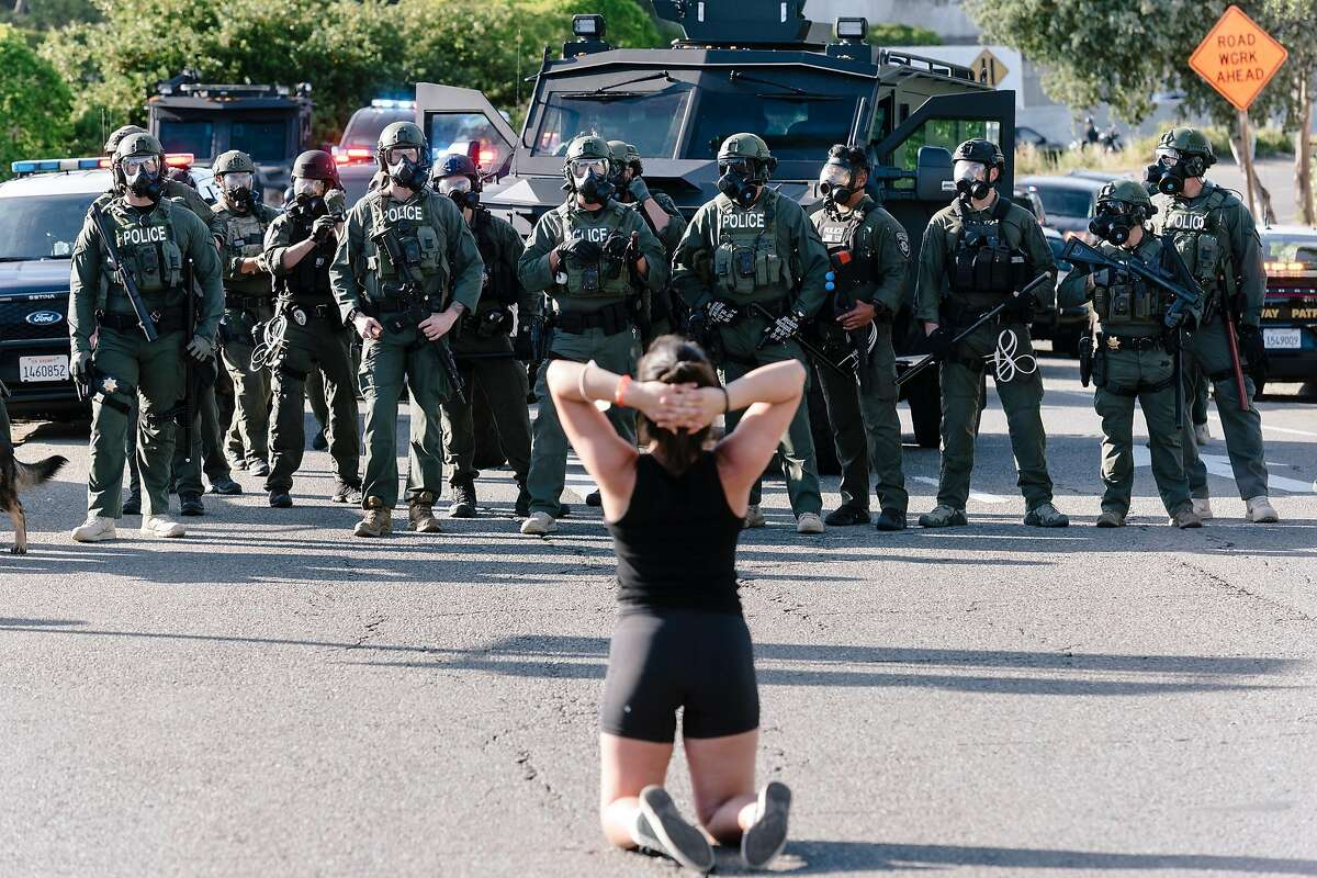 A protestor kneels in front of a line of police blocking the entrance to Interstate 680 in Walnut Creek, Calif, on Monday, June 1, 2020.