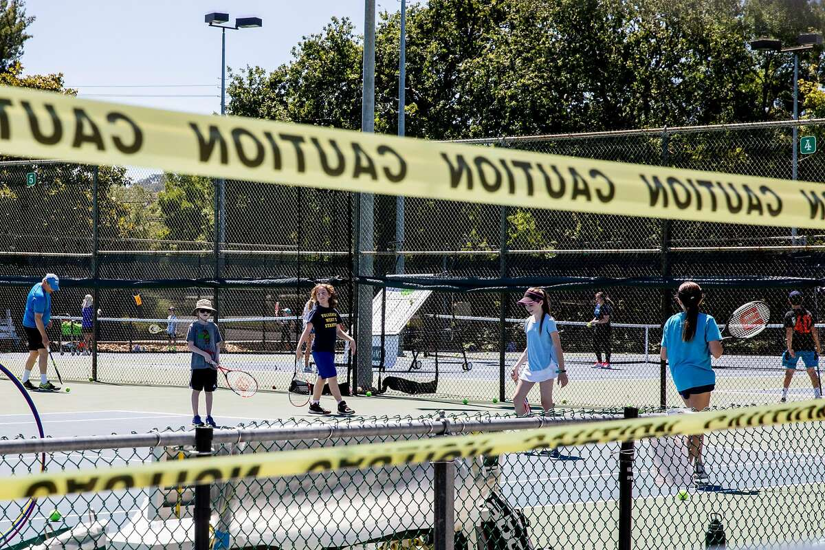Kids practice their tennis skills at a day camp at the Heather Farm Park tennis courts in Walnut Creek, Calif. Tuesday, June 9, 2020. They Bay Area is opening at a fairly fast pace, with Contra Costa County announcing plans this week to reopen indoor dining and hair salons soon, while it reports near-record new cases.
