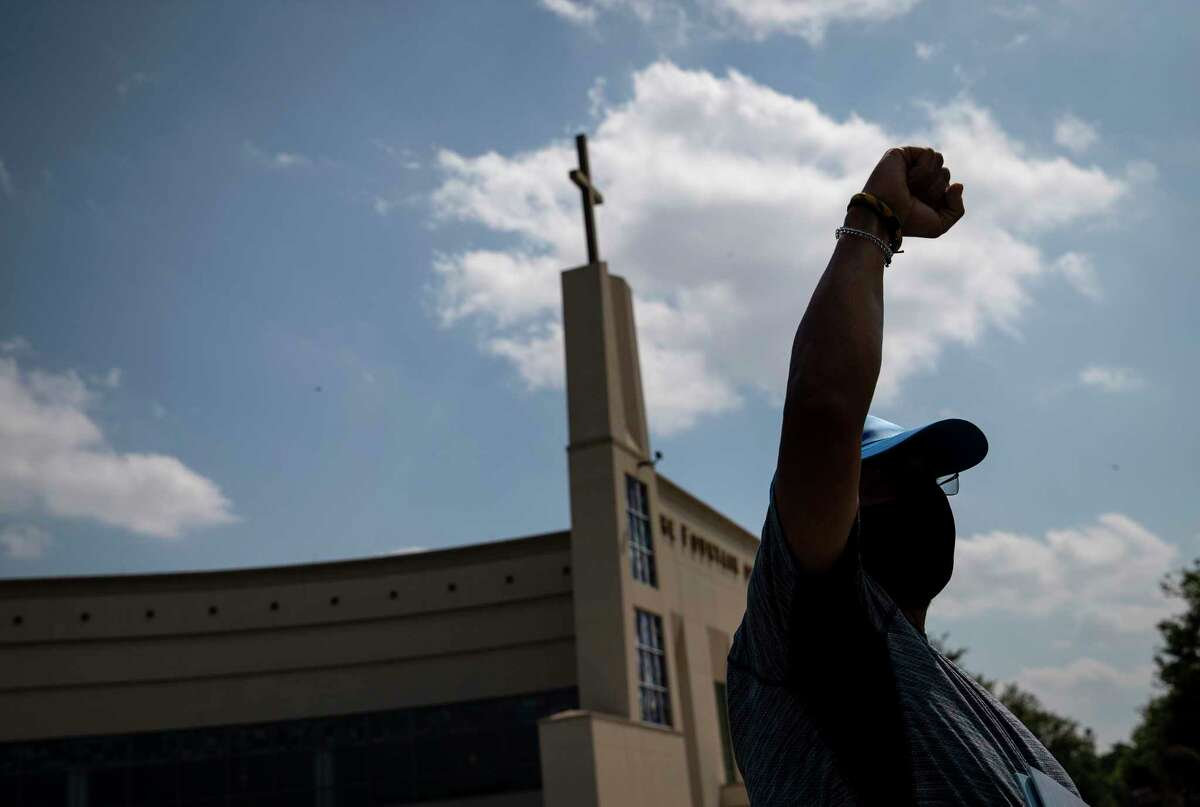 """Alfred Jacobs gestures as the body of George Floyd leaves the church during a private funeral for Floyd on Tuesday, June 9, 2020, at The Fountain of Praise church in Houston. Jacobs said he grew up in South Africa. """"America was a big source of inspiration for us, and it breaks my heart because we did this 60 years ago,"""" he said. """"I don't want my grandchildren to go through this."""""""