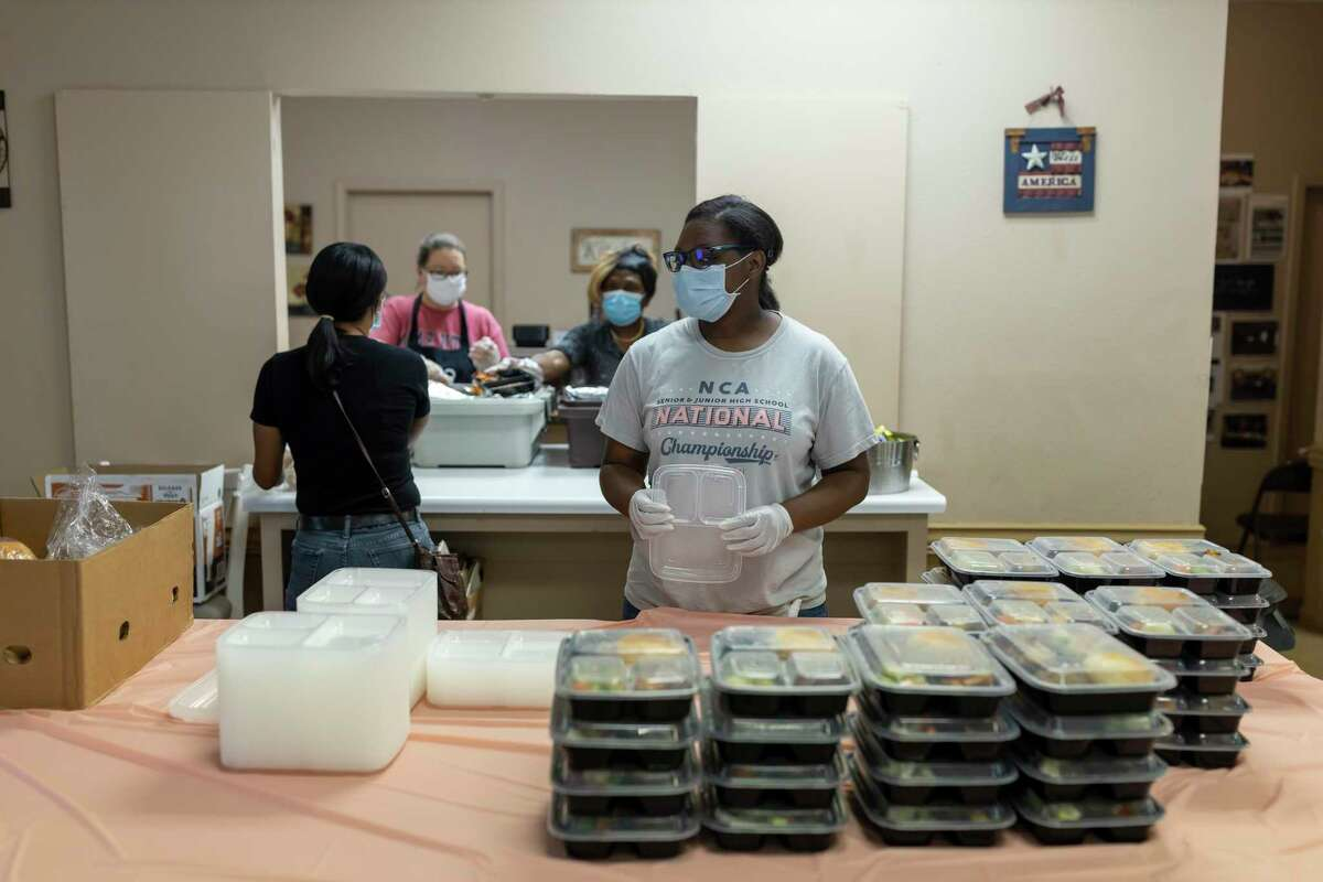 A volunteer waits to add tops to packaged hot meals at the Sleepy Hollow Multipurpose Building in Tamina, Wednesday, May 13, 2020. Volunteers were able to distribute an estimated 150 hot meals that were provided by Meals on Wheels. With the new funding from the United Way of Greater Houston and the Greater Houston Community Foundation, Meals on Wheels will be able to provide 1,000 meals a week to new clients.