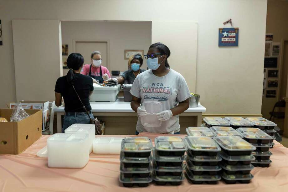 A volunteer waits to add tops to packaged hot meals at the Sleepy Hollow Multipurpose Building in Tamina, Wednesday, May 13, 2020. Volunteers were able to distribute an estimated 150 hot meals that were provided by Meals on Wheels. With the new funding from the United Way of Greater Houston and the Greater Houston Community Foundation, Meals on Wheels will be able to provide 1,000 meals a week to new clients. Photo: Gustavo Huerta, Houston Chronicle / Staff Photographer / Houston Chronicle © 2020