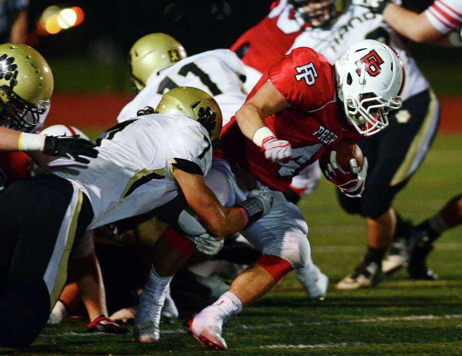 Fairfield Prep's Joseph Ganim is tackled by Daniel Hand's Scott Sweitzer, during football action in Fairfield, Conn. on Friday October 17, 2014. Coming in from behind is Hand's Cory Walsh. Photo: Christian Abraham / Christian Abraham / Connecticut Post