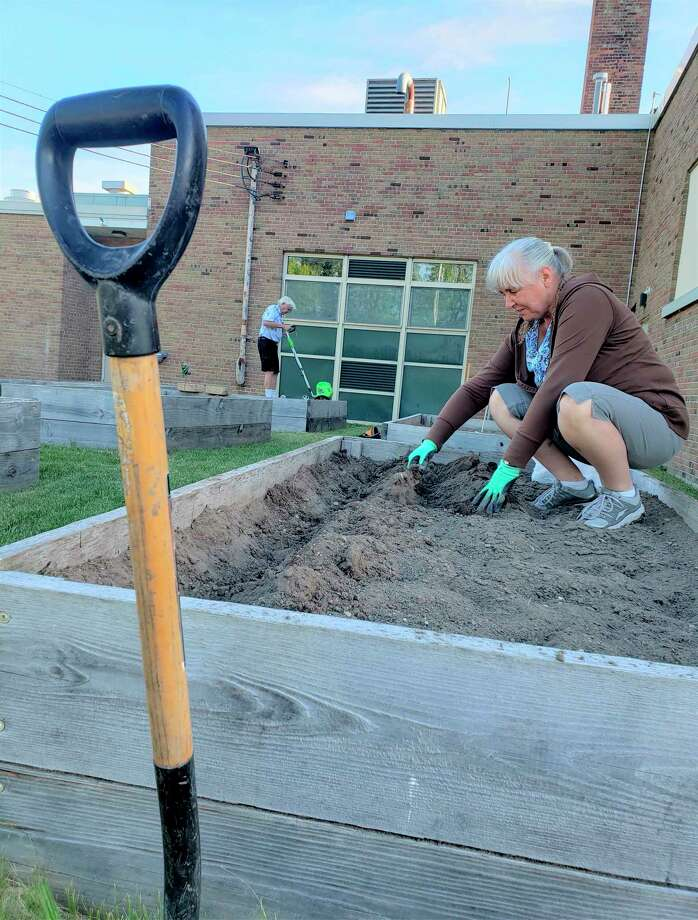 Tuesday morning, volunteers could be seen preparing soil in the raised garden beds and planting seedlings at the Armory Youth Project on First Street. The crops are meant to be grown for fruits and vegetables for Manistee County food pantries. (Arielle Breen/News Advocate)