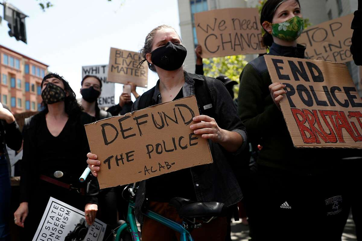 A protester holds a Defund the Police sign outside Oakland Police Headquarters in Oakland, Calif., on Sunday, June 7, 2020.